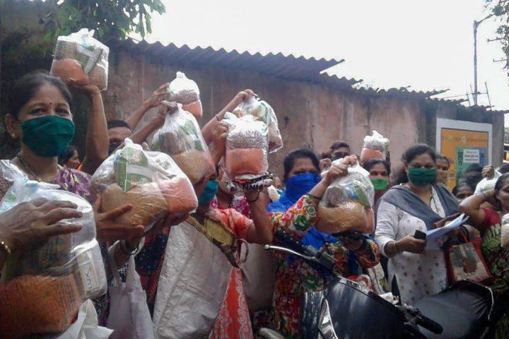Bewohner eines Slums in Mumbai mit Hilfspaketen von Seek and Care